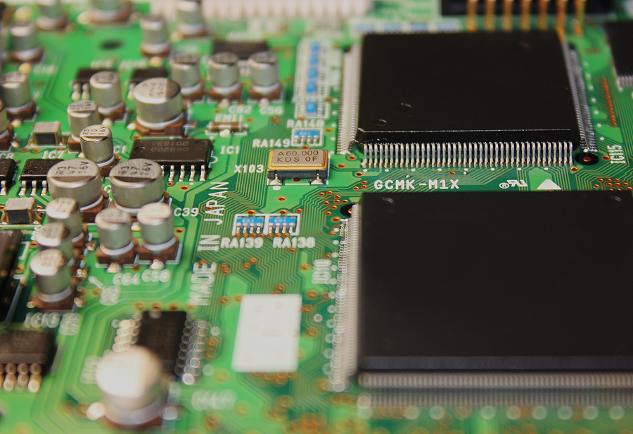 Close up photo of a green printed circuit board.