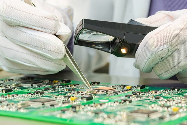 Technician working on circuit board.