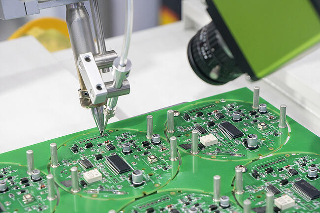Close up of a printed circuit board being assembled.