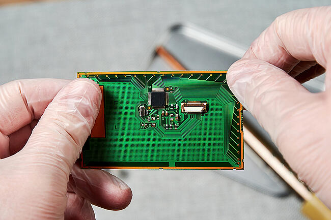Engineer looking closely at a printed circuit board.