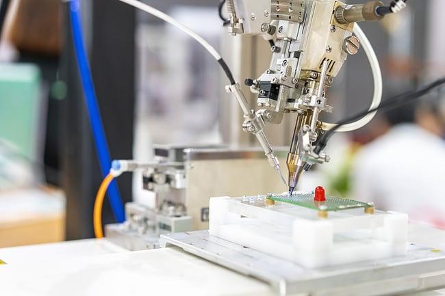 Robotic arm assembling a medical device PCB.